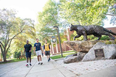 Students walking by panther statue
