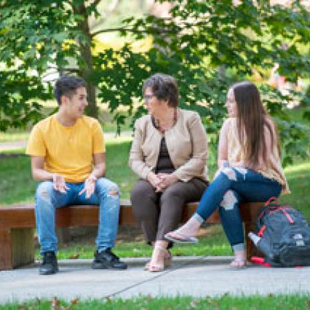 Catherine Koverola sitting on bench with students
